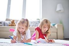Милые маленькие девочки рисуя на поле стоковые фото