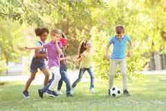 Милые маленькие дети играя с шариком outdoors стоковое фото