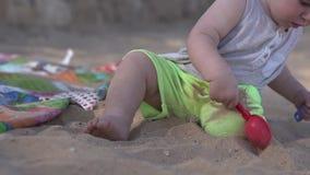 Милые маленькие игры младенца на пляже с затвором, грабл и песком сток-видео