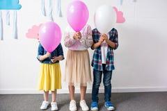 милые маленькие ребеята держа воздушные шары пока стоящ совместно на вечеринке по случаю дня рождения Стоковое Изображение RF