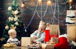 Милые маленькие ребята празднуя рождество Концепция зимнего отдыха Xmas рождества Смешной ребенк держа подарок рождества babette стоковое изображение rf
