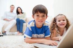 Милые малыши играя компютерные игры на компьтер-книжке Стоковая Фотография RF