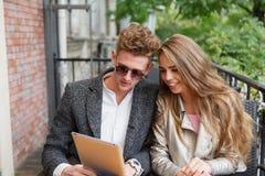 Милые молодые влюбчивые пары с цифровой таблеткой на запачканной предпосылке новая технология принципиальной схемы Стоковые Фотографии RF