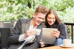 Милые молодые влюбчивые пары с цифровой таблеткой на запачканной предпосылке новая технология принципиальной схемы Стоковая Фотография RF