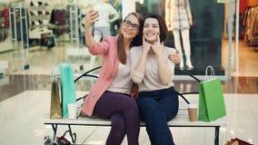 Милые молодые женщины принимают selfie используя камеру смартфона сидя на стенде в торговом центре и имея потеху самомоднейше сток-видео