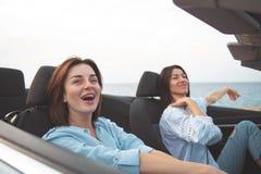 Милые молодые женщины усмехаются в автомобиле Стоковое фото RF