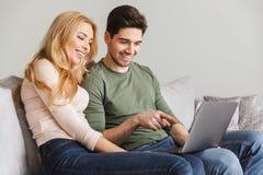 Милые молодые любящие пары сидя на софе используя портативный компьютер Стоковое фото RF