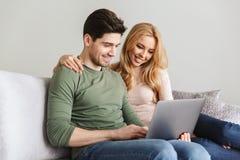 Милые молодые любящие пары сидя на софе используя портативный компьютер Стоковая Фотография RF