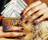 Милые пальцы Афро-американской женщины держа деньги близкий вверх с портмонем, роскошными украшениями на муфте питона Стоковое фото RF