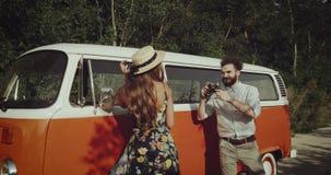 Милые пары фотографируя используя винтажную камеру фото около ретро шины, женщины нося винтажные платье и шляпу видеоматериал