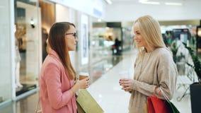Милые подруги беседующ и смеющся в торговом центре держа takeout напитки и красочные бумажные мешки радостно сток-видео