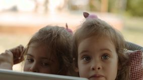 Милые сестры держат таблетку и наблюдают шарж на ем акции видеоматериалы