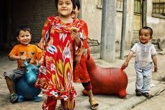 милые смешные местные дети играя с раздувными игрушками хвастуна на улице стоковые фото