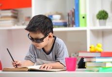 Милые солнечные очки маленького ребенка нося и делать чтение домашней работы Стоковые Изображения RF