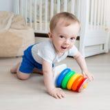 Милые 10 старого месяцев мальчика малыша вползая на поле и смотря в камере Стоковые Изображения RF