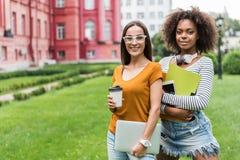 Милые студентки стоя с устройствами стоковая фотография