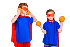 милые супер дети в масках и плащи держа апельсины стоковое фото rf