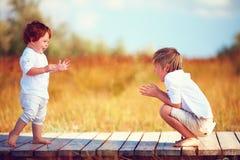 Милые счастливые дети, братья играя совместно на поле лета Стоковое Изображение RF
