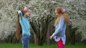 Милые усмехаясь друзья делая стиль причесок на открытом воздухе Концепция заботы и красоты тела сток-видео