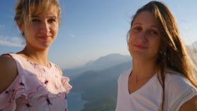 Милые усмехаясь женщины с горным видом на предпосылке сток-видео