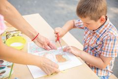 Милые формы вырезывания мальчика из покрашенной бумаги Был творческое, превращаясь воображение, творческие способности, сделайте  стоковое изображение rf