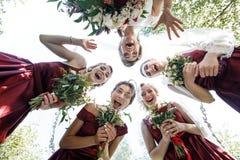 Милые bridesmaids окружают невесту держа bouqeuts свадьбы в их оружиях стоковое изображение rf