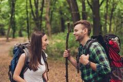 Милые excited любовники пеший в лесе весны, говоря и наслаждаясь, нося удобные обмундирования для пешего туризма, с рюкзаками стоковые фото