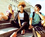 Милые teenages группы на здании университета с huggings книг Стоковое Изображение RF