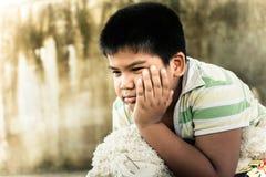 Милый азиатский мальчик унылый самостоятельно в парке, винтажном тоне Стоковое фото RF