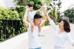 Милый азиатский отец перевозить его сына вместе с его женой в парке Excited руки повышения семьи вместе с счастьем стоковое изображение