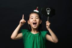 Милый азиатский ребенок девушки одел в зеленом платье держа ручку шарика идеи с украшением головы рождества на черной предпосылке Стоковые Фото