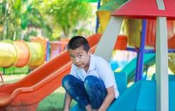 Милый азиатский ребенок имея потеху на спортивной площадке Стоковые Изображения RF