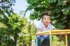 Милый азиатский ребенок имея потеху на спортивной площадке Стоковое фото RF