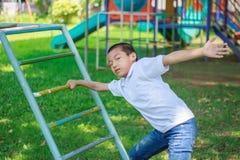 Милый азиатский ребенок имея потеху на спортивной площадке Стоковое Фото
