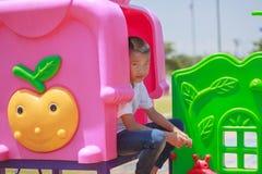 Милый азиатский ребенок имея потеху на спортивной площадке Стоковые Изображения