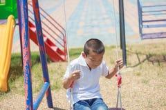 Милый азиатский ребенок имея потеху на спортивной площадке Стоковая Фотография