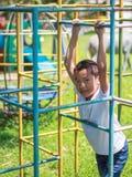 Милый азиатский ребенок имея потеху на спортивной площадке Стоковые Фотографии RF