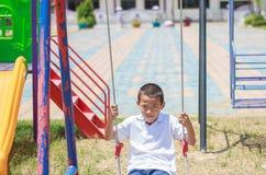 Милый азиатский ребенок имея потеху на спортивной площадке Стоковое Изображение