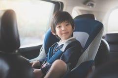 Милый азиатский ребенок сидя в автокресле стоковая фотография