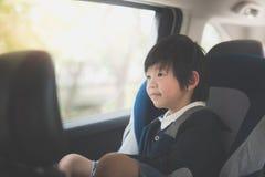 Милый азиатский ребенок сидя в автокресле стоковое фото rf