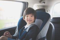 Милый азиатский ребенок сидя в автокресле стоковые фото