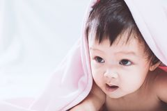 Милый азиатский ребёнок усмехаясь под розовым одеялом Стоковая Фотография RF