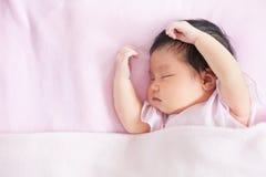 Милый азиатский newborn ребёнок спать в кровати Стоковое Изображение RF