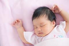 Милый азиатский newborn ребёнок спать в кровати Стоковое Фото
