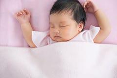 Милый азиатский newborn ребёнок спать в кровати Стоковая Фотография