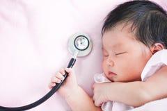 Милый азиатский newborn ребёнок спать и держа стетоскоп Стоковые Изображения