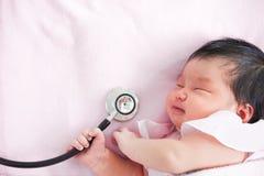 Милый азиатский newborn ребёнок спать и держа стетоскоп Стоковая Фотография