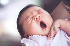 Милый азиатский newborn ребёнок спать и зевая на руке ` s матери Стоковое Фото
