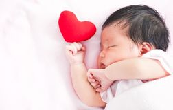 Милый азиатский newborn ребёнок спать с красным сердцем Стоковое Изображение