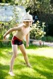 Милый активный мальчик ребенк скача в сад на теплый солнечный летний день Счастливый ребенк смотря камеру Прелестный ребенок с стоковые фото